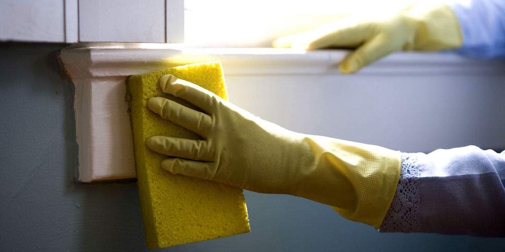 Feature image of a window sill being cleaned with sponge and rubber gloves.